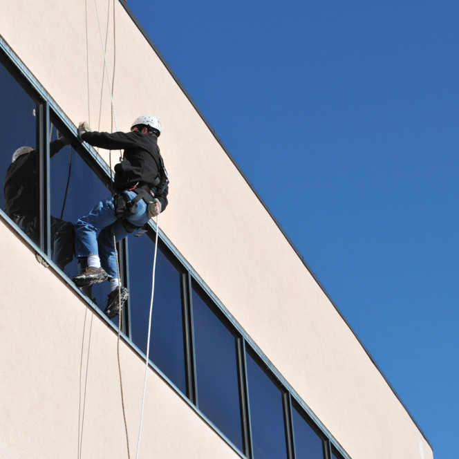 Man hanging from hundreds of feet up in the air requires a rope access structural assessment.